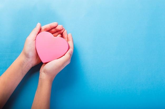 Mains féminines tenant un coeur rose sur fond bleu clair.