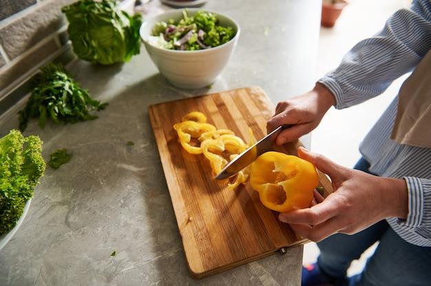 Mains féminines tenant un couteau et coupant le poivron jaune en anneaux. vue grand angle. fermer.