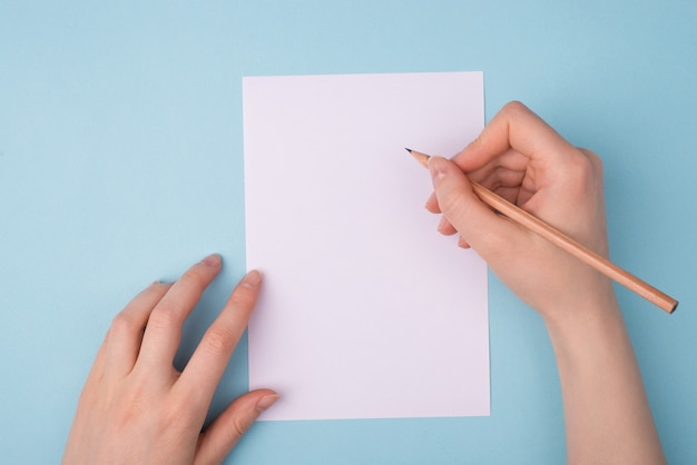 Mains féminines tenant un crayon sur une feuille de papier blanc