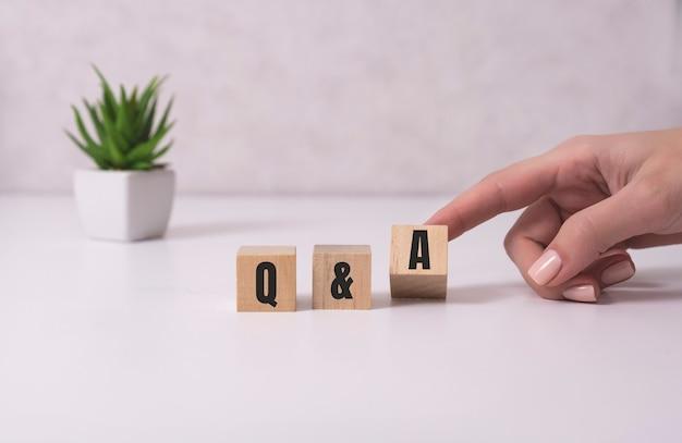 Mains féminines tenant des cubes en bois avec le texte q&a, questions et réponses