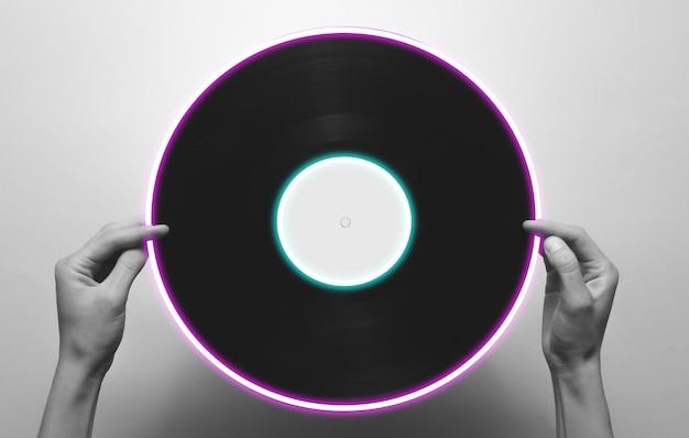 Mains féminines tenant un disque vinyle rétro