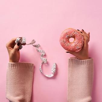 Mains féminines tenant donut et ruban à mesurer sur fond rose.