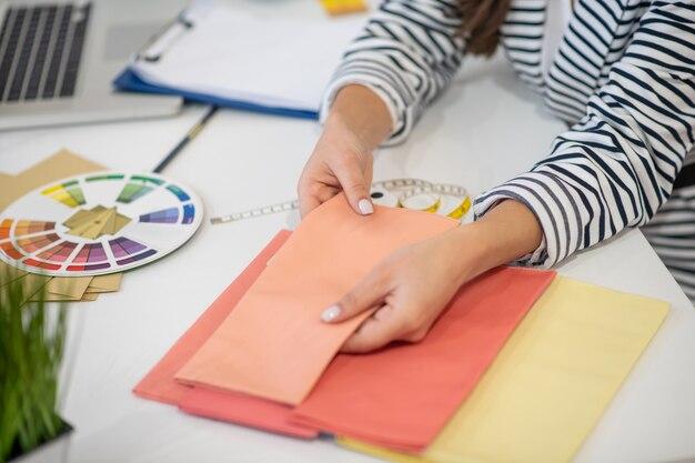 Mains féminines tenant un échantillon de tissu orange tout en vérifiant les matériaux