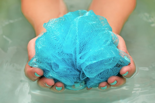 Mains féminines tenant un gant de toilette synthétique doux et rond dans un bain avec de l'eau. gros plan sur les mains. cure thermale, soins du corps, fond d'eau.