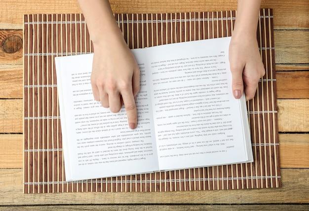 Mains féminines tenant un livre ouvert sur un tapis