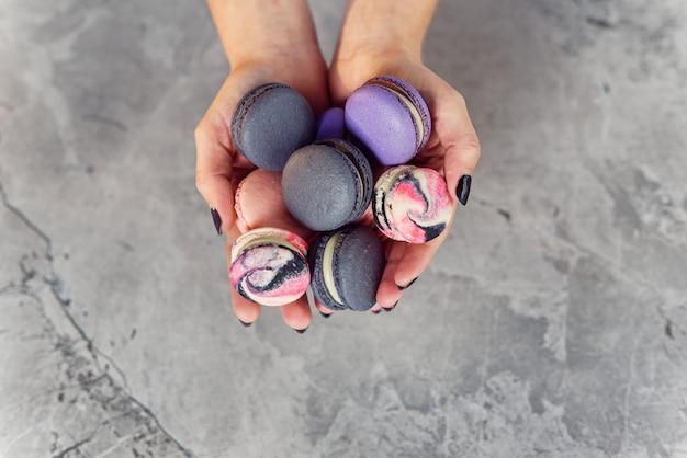 Mains féminines tenant des macarons français colorés sur une table en marbre. vue de dessus.