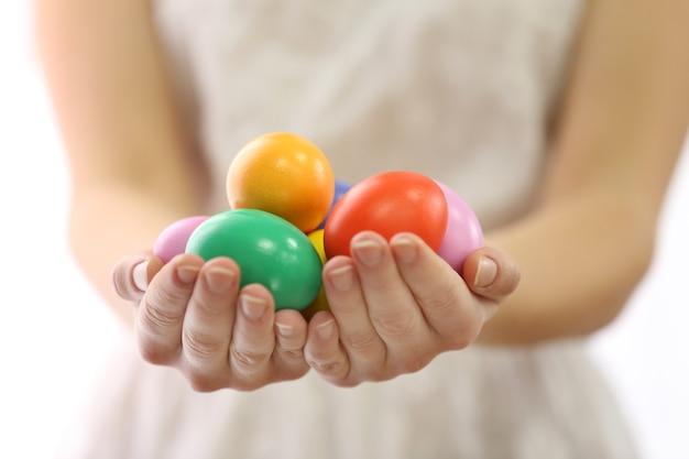 Mains féminines tenant des oeufs de pâques isolés sur blanc