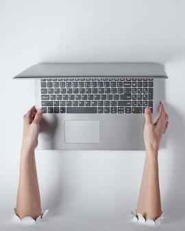 Mains féminines tenant un ordinateur portable à travers les trous