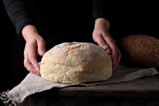 Mains féminines tenant un pain de farine de blé cuit au four