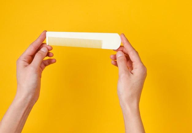 Mains féminines tenant un peigne en plastique blanc sur jaune. soins capillaires, concept de beauté. vue de dessus