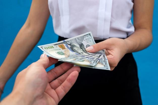 Mains féminines tenant pile d'argent isolé sur fond bleu