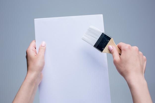 Les mains féminines tenant un pinceau sur toile blanche