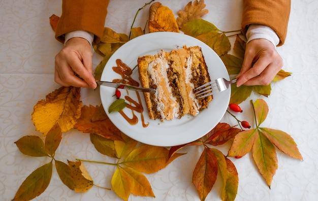 Mains féminines tenant la plaque blanche avec un gâteau