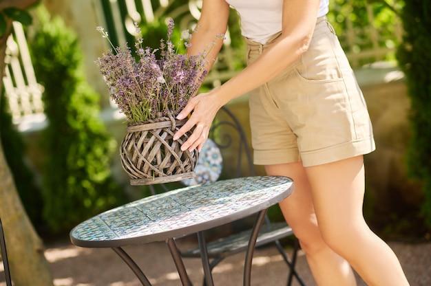 Mains féminines tenant un pot de fleurs sur une table