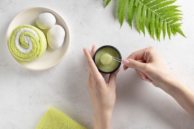 Mains féminines tenant un pot ouvert et une cuillère avec un gommage. concept de soins corporels quotidiens, produits de bain bio. mur de béton blanc avec feuille de fougère verte. vue de dessus.