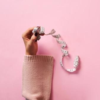 Mains féminines tenant le ruban à mesurer sur fond rose.