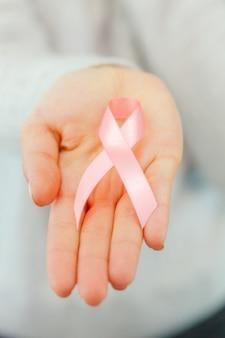 Mains féminines tenant un ruban de sensibilisation au sida