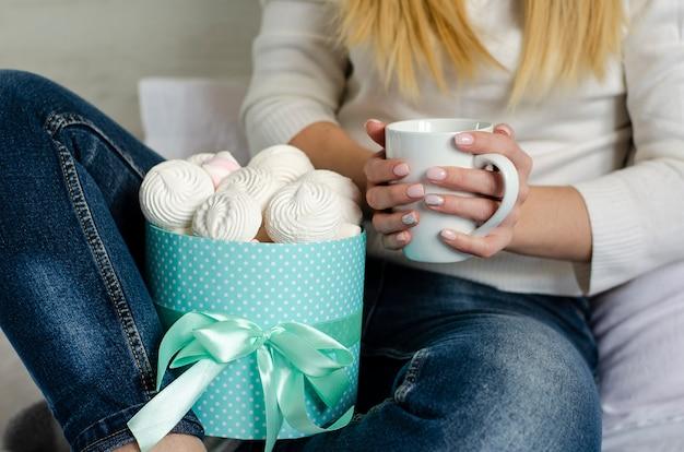 Mains féminines tenant une tasse blanche avec café au lait. guimauves et meringues dans une boîte
