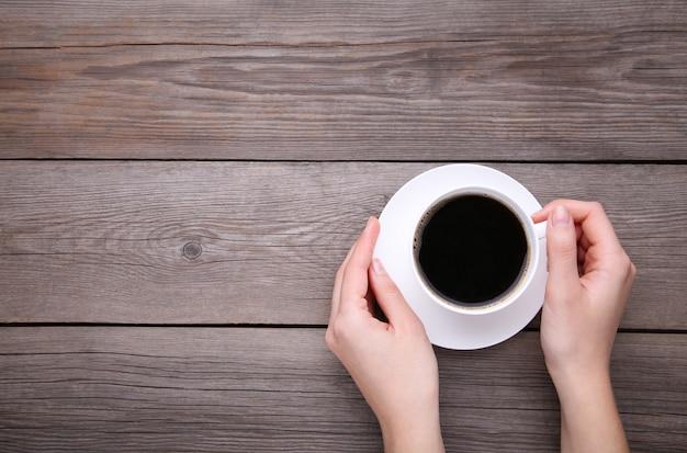 Mains féminines tenant la tasse de café sur un fond en bois gris.