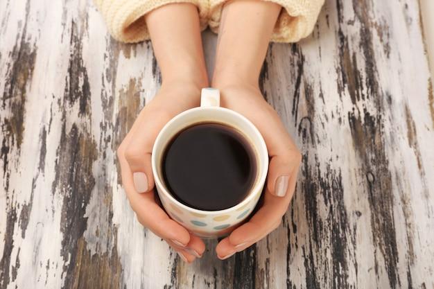 Mains féminines tenant une tasse de café sur fond de bois