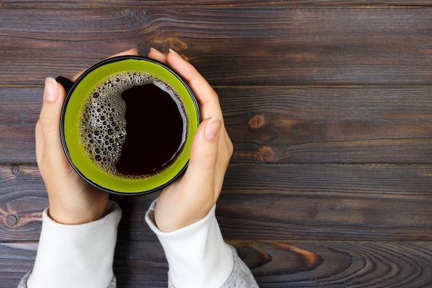 Mains féminines tenant une tasse de café sur fond de table en bois rustique