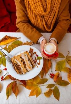 Mains féminines tenant une tasse de café rouge près de feuilles d'automne de gâteau