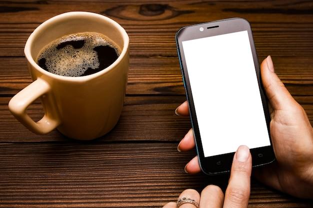 Mains féminines tenant une tasse de café sur une table en bois