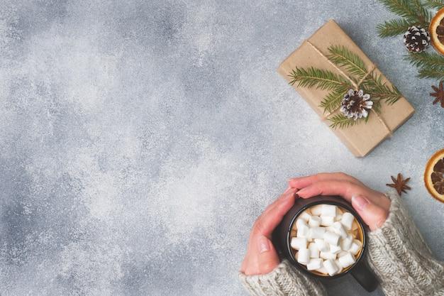 Mains féminines tenant une tasse de chocolat chaud et de guimauves sur fond gris