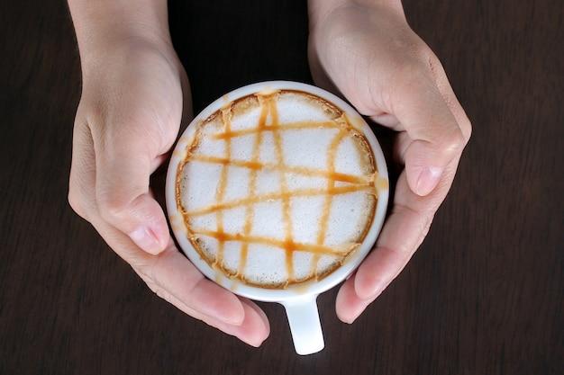 Mains féminines tenant la tasse de macchiato au caramel sur fond en bois