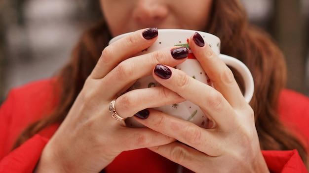 Mains féminines tenant une tasse de noël avec une boisson chaude et noire à l'extérieur le jour de l'hiver