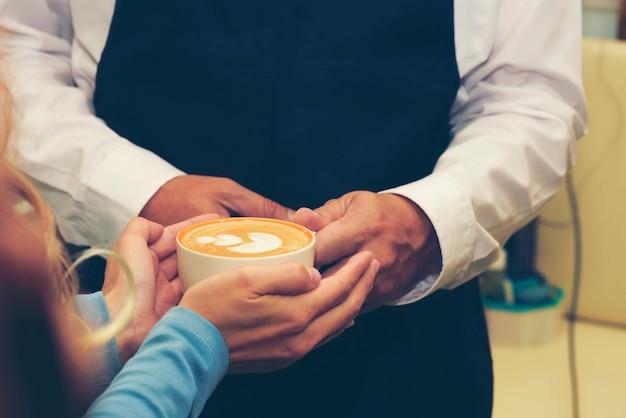 Mains féminines tenant des tasses de café