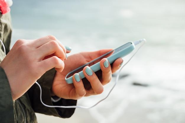 Mains féminines tenant un téléphone portable bleu avec les écouteurs connectés sur fond de la mer