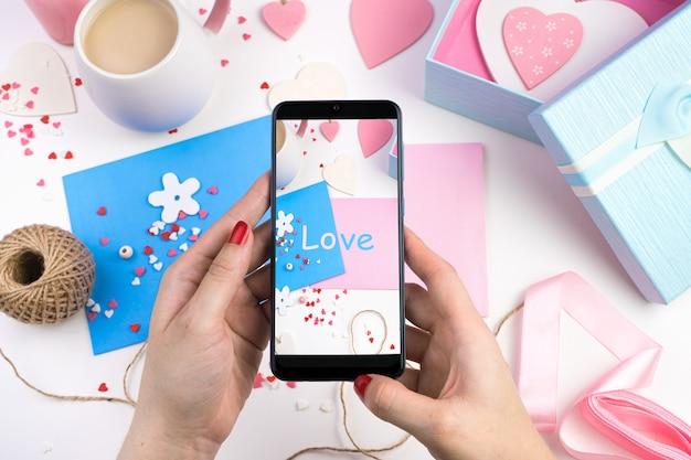 Mains féminines tenant le téléphone et prendre des photos de fond romantique.