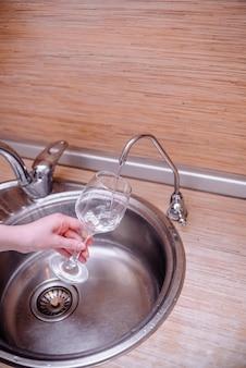 Mains féminines tenant un verre de vin avec de l'eau.