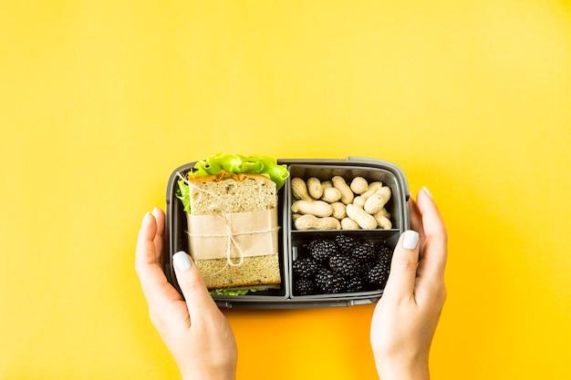 Mains féminines tenir la boîte à lunch avec de la nourriture