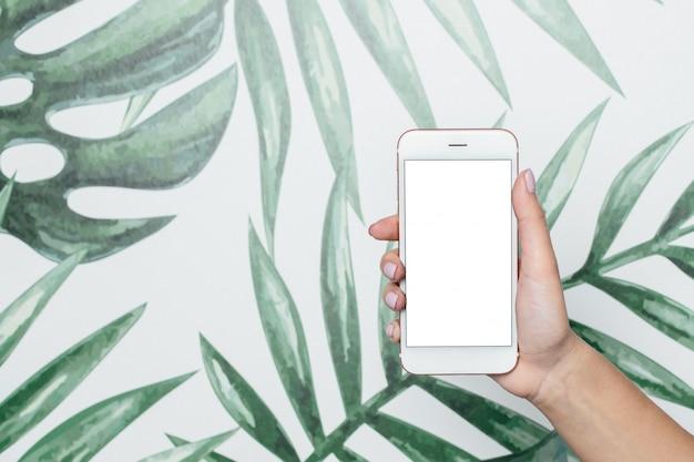 Mains féminines tenir un téléphone mobile avec des feuilles d'écran blanc