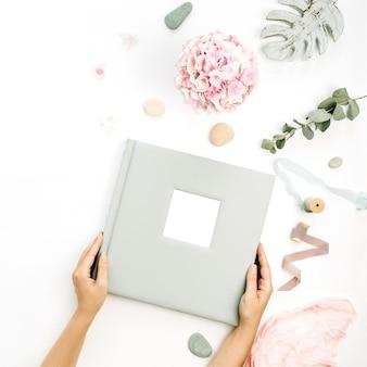 Des mains féminines tiennent un album photo de mariage ou de famille