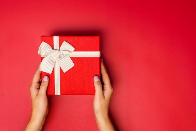 Les mains féminines tiennent une boîte ou une boîte cadeau avec un ruban d'or sur fond rouge