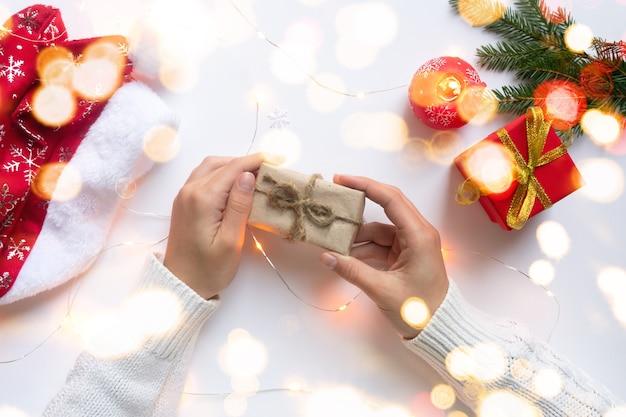Des mains féminines tiennent une boîte-cadeau artisanale attachée avec une corde de jute. concept de cadeaux pour noël