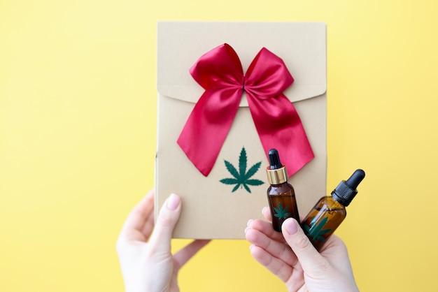 Les mains féminines tiennent une boîte-cadeau et une bouteille de marijuana