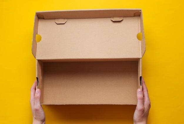 Les mains féminines tiennent une boîte en carton vide sur jaune. vue de dessus