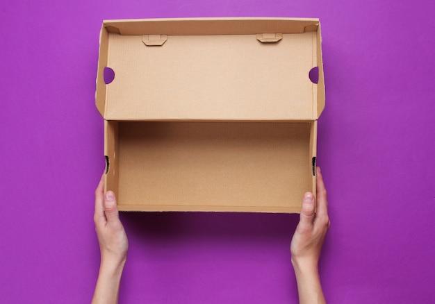 Les mains féminines tiennent une boîte en carton vide sur violet. vue de dessus