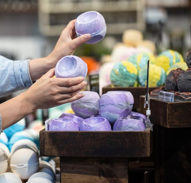 Des mains féminines tiennent des bombes de bain lumineuses dans un magasin de cosmétiques. concept de soins du corps.