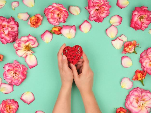 Des mains féminines tiennent coeur rouge, fond vert avec des pétales de roses roses