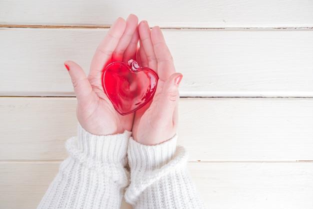 Les mains féminines tiennent un coeur en verre rouge. carte de voeux de la saint-valentin. concept de soins et de santé, soins de santé, espace de copie de vue de dessus de thème de santé cardiaque