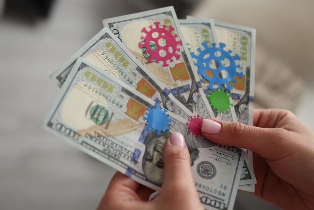 Des mains féminines tiennent dans la main des billets d'un dollar infectés par une infection à coronavirus