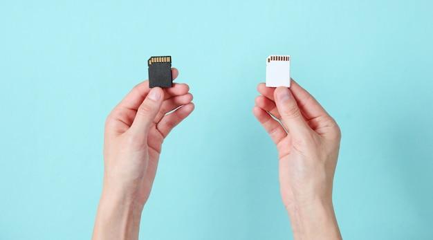 Les mains féminines tiennent deux cartes mémoire sd sur bleu. concept techno minimaliste.