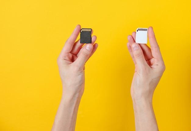 Les mains féminines tiennent deux cartes mémoire sd sur jaune. concept techno minimaliste.