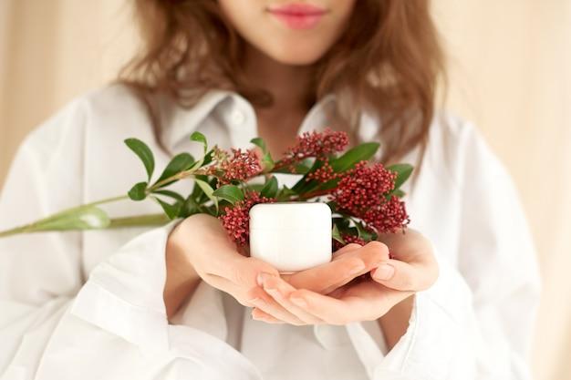 Les mains féminines tiennent doucement le pot blanc de crème. maquette de concept de cosmétiques