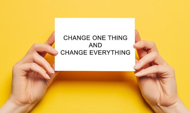 Des mains féminines tiennent du papier cartonné avec du texte changez une chose et changez tout sur fond jaune. concept commercial et financier